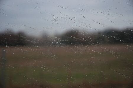 Close up of rain on a window with a blurry field and forest in the background