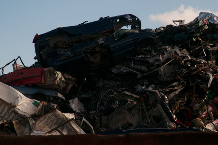 Photo of a heap of smashed cars and old metal in a junkyard with a blue sky and clouds in the background Stock Photo