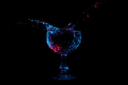 Water being poured into and splashing out of a glass in red and blue highlights isolated on a black background