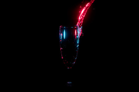 Stream of water highlighted in bright red being poured into a champagne glass isolated on a black background