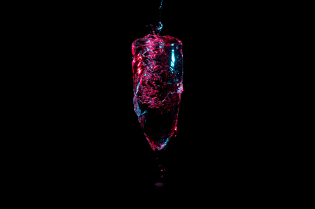 Water under red lights being poured into a champagne glass from above isolated on a black background