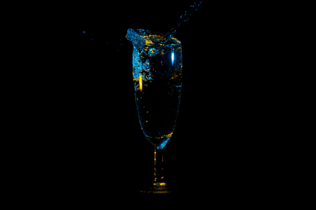 Water splashing out of a tall wine glass under yellow and blue lights isolated on a black background