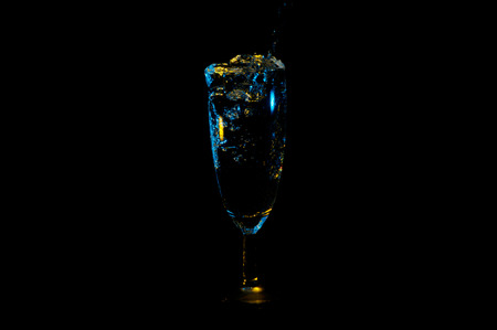 Beverage being poured into a fancy glass and bubbles spilling over the edge under yellow and blue lights isolated on a black background
