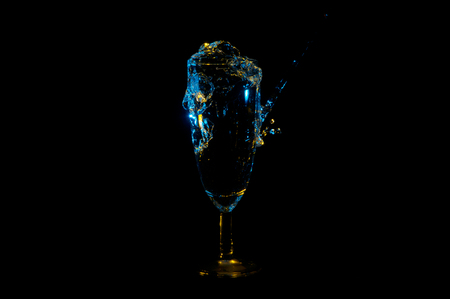 Beverage being poured and splashing from a full fancy stemmed flute glass under yellow and blue lights isolated on a black background