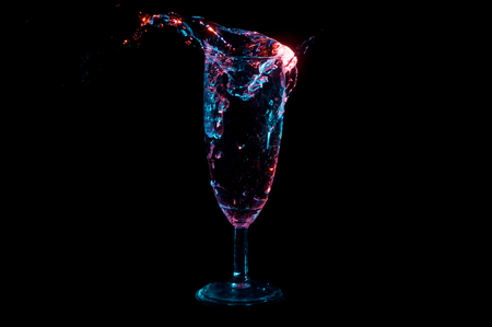Water being thrown into a full glass and making a big splash under blue and red lights isolated on a black background