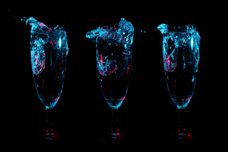 Splashes and bubbles of clear liquid lit in blue lights with red accent lights in a row of three identical fancy stemmed glasses on a black background