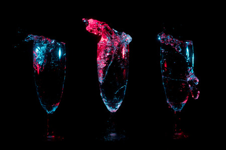 Beverage splashing into three separate champagne flutes under red and blue lights on a black background