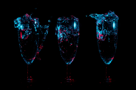 Blue lights with red accents highlight splashes and bubbles of liquid into a row of three identical fancy glasses on a black background