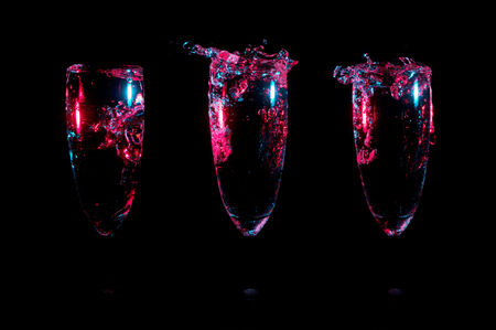 Small splashes of clear liquid glowing with bright red light and blue highlights in three identical glasses in a row on a black background Stock Photo