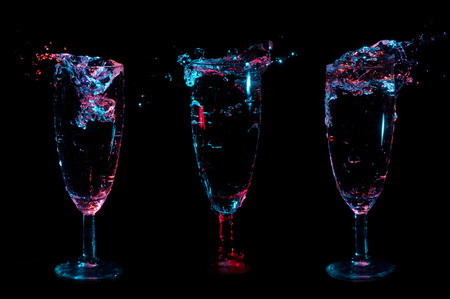 Blue and red lit splashes of clear liquid in three fancy glasses in a row on a black background Stockfoto