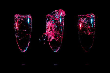 Illuminated red bubbles and splashes of clear liquid with subtle blue highlights in a row of three oblong glasses on a black background Stock Photo