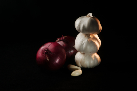 Composition with two red onions and a stack of three heads of garlic with two garlic cloves in front of them on a black background