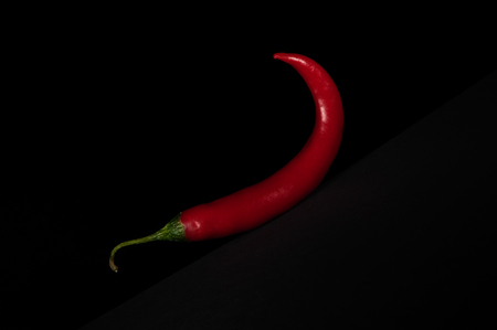 One vibrant bright red chili pepper isolated on a black background 免版税图像