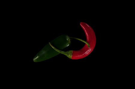 A green jalapeno pepper overlapping with a bright red chili pepper isolated on a black background