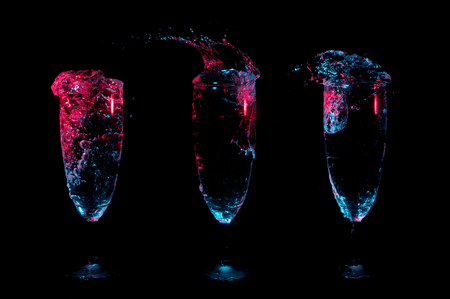 Three glasses in a row with different splashes of clear beverages under red and blue lights on a black background