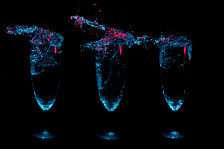 Three fancy glasses in a row full of liquid and with big splashes over the top under blue lights with red highlights on a black background
