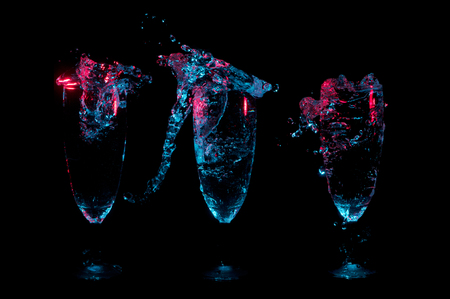 Three fancy glasses in a row each with a different big splash of liquid under blue and red lights on a black background Zdjęcie Seryjne