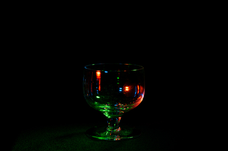 Fancy empty glass in colorful lights isolated on a black background