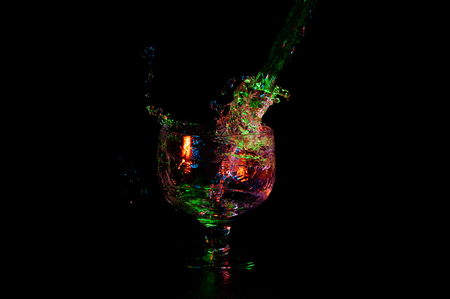 Alcohol being poured in fancy wine glass on a dark background with colorful lights Stock Photo