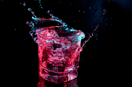 Water splashing out from a rocks glass in colored lights isolated on a black background