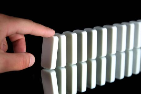 toppled: a row of dominoes about to be toppled Stock Photo