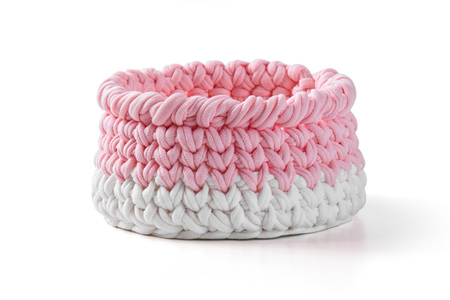 Wicker basket made of pink fabric. Isolated image on white background Standard-Bild