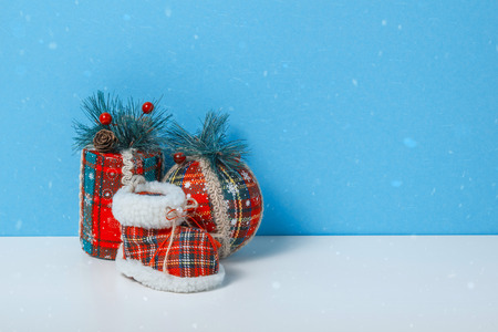 Christmas tree toy ball, cylinder, sock. Holiday celebration concept on a blue background.