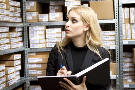 inventory: Sexy mujer joven haciendo inventario studio disparo Foto de archivo