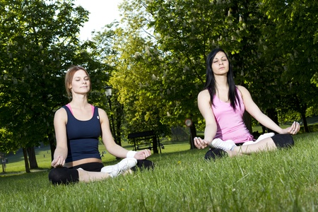 Young girls doing yoga in the park Stock Photo - 9390335