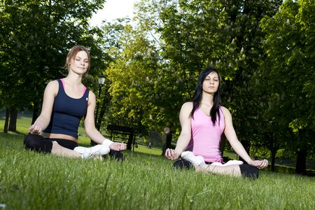 Young girls doing yoga in the park photo