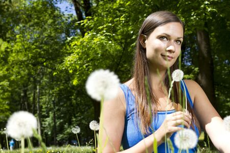 Beautiful young girl in the park smelling dandelion photo