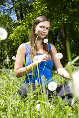 Beautiful young girl in the park smelling dandelion Stock Photo