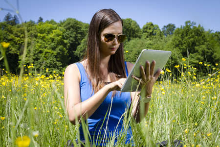 Beautiful young Girl in the Park with Tablet PC