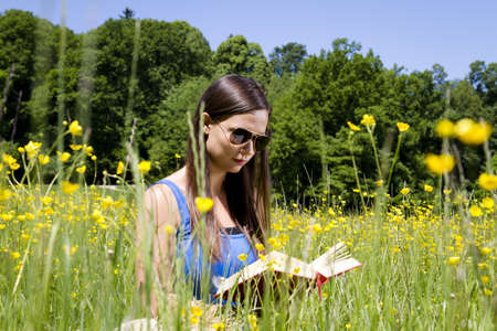 Beautiful young girl in the park reading a book