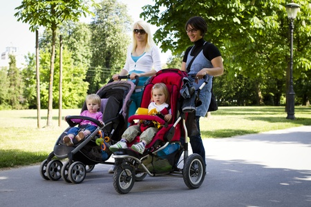 Young mothers walking in the park with strollers Stock Photo