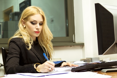 Secretary in the office writing a letter photo