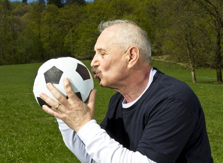 Senior football player kissing his ball Stock Photo
