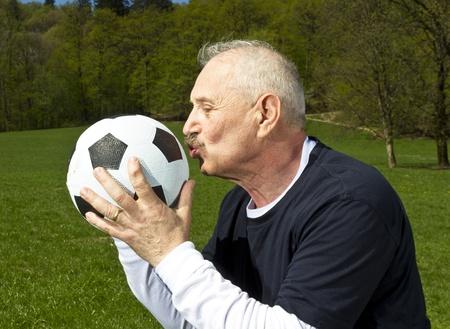 Senior football player kissing his ball Stock Photo