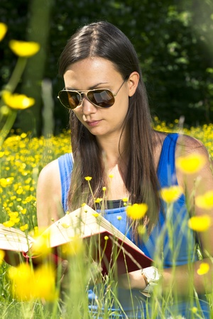 Girl reading a book in the park Stock Photo
