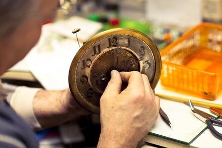 craftman: Clockmaker in his workshop repairing Stock Photo
