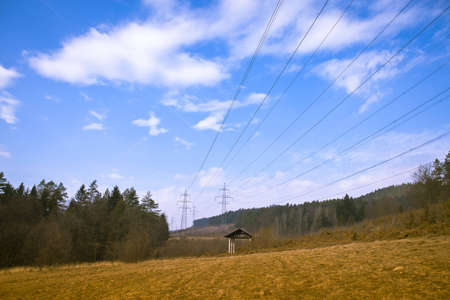 long lines of powerline towers stretching across a beautiful countryside Stock Photo