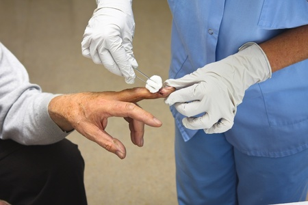 Patient at doctor office getting his finger stitched