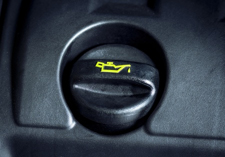 motor oil: Oil cap on the engine cover with yellow logo Stock Photo