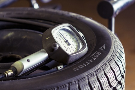 Pressure meter on a flat tire Stock Photo