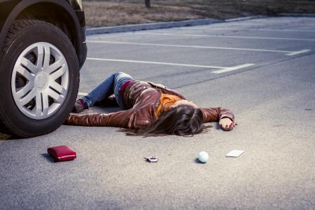 crash car: Woman lying injured on the pavement Stock Photo