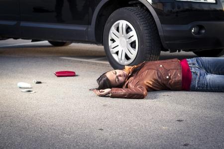 Woman lying injured on the pavement Stock Photo