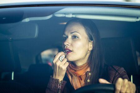 Woman applying makeup while driving Stock Photo