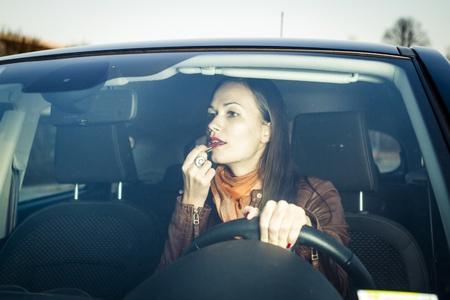 mujer maquillandose: Mujer de aplicar el maquillaje mientras se conduce Foto de archivo