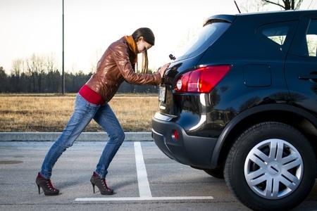 Young woman pushing broken car Stock Photo