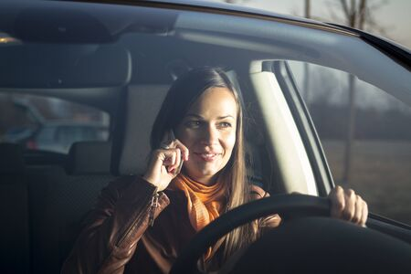 woman driving car: Woman talking on the phone while driving
